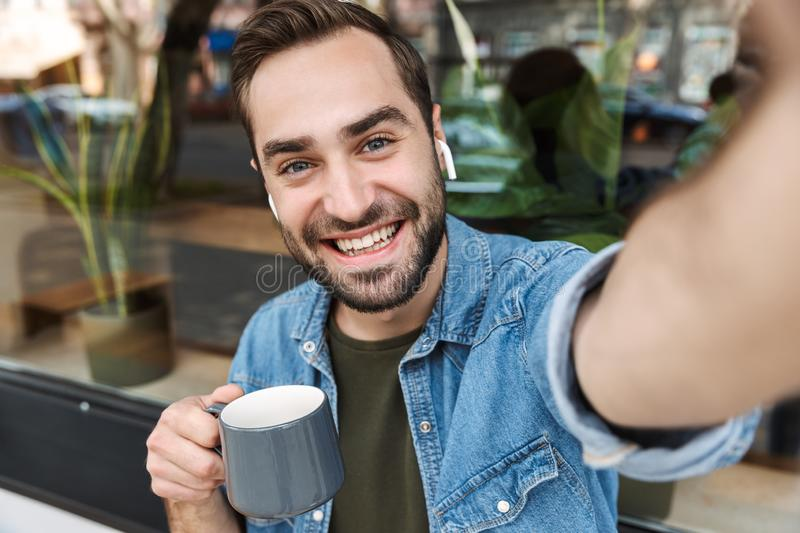 Photo of handsome young man drinking cup of coffee while taking selfie on smartphone in city cafe outdoors royalty free stock photo
