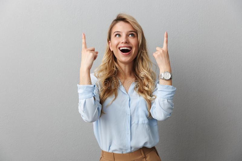 Photo of happy blond businesswoman with long curly hair smiling and pointing fingers upward at copyspace stock image