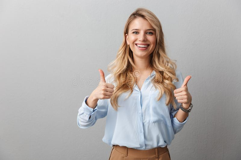 Photo of happy blond businesswoman with long curly hair smiling and showing thumbs up royalty free stock images
