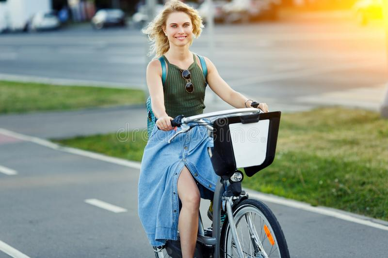 Photo of happy blonde in long denim skirt riding bike on road in city on summer day royalty free stock photo