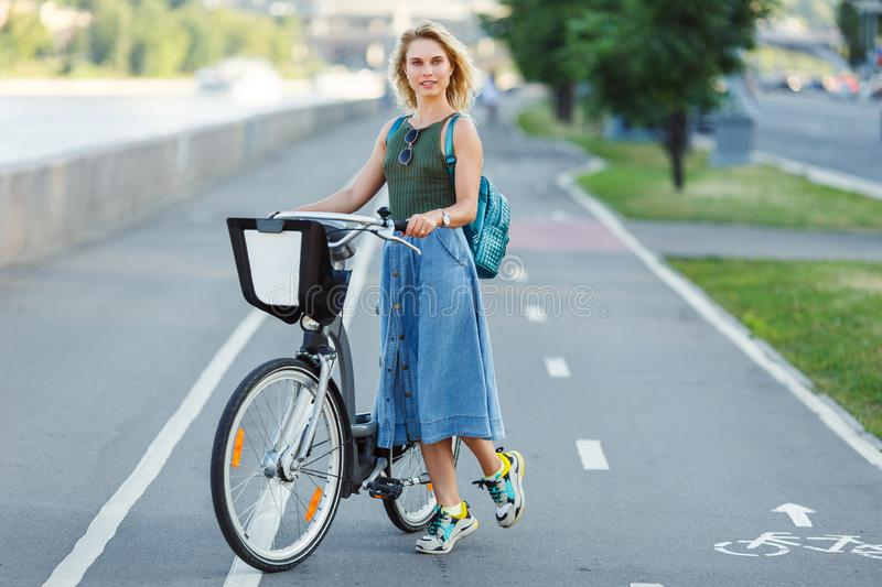 Photo of happy blonde in long denim skirt standing next to bike on road in city royalty free stock photo