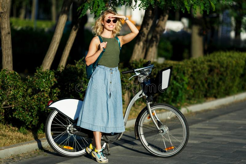 Photo of happy blonde in long denim skirt standing next to bike on road next to green bushes in city stock photos