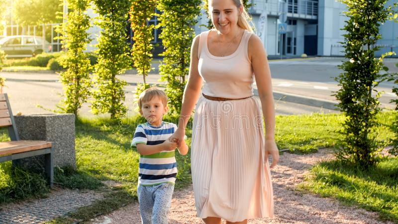 Photo of happy cheerful toddler boy with young mother walking and running on playground at park stock photos