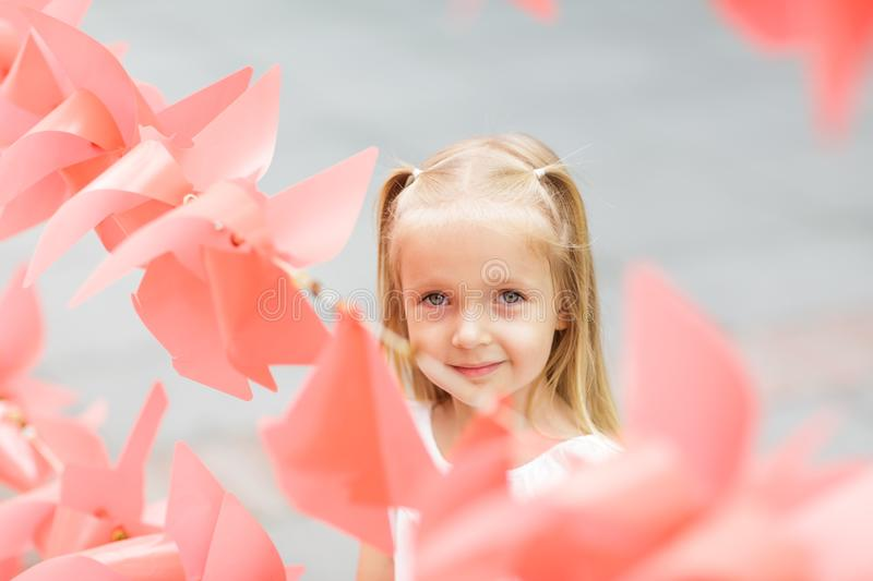 Photo of a happy child, a little blonde girl in nature, on a walk in the park stock photo