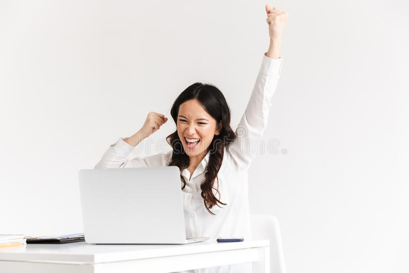 Photo of happy chinese businesswoman with long dark hair screaming with raised arms while working with documents and stock image