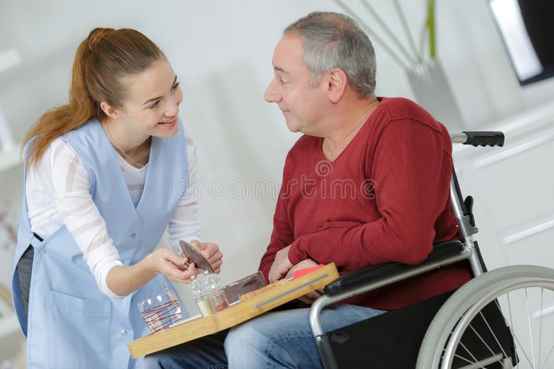 Photo happy elderly man with disability and helpful nurse. Photo of happy elderly men with disability and helpful nurse stock photography