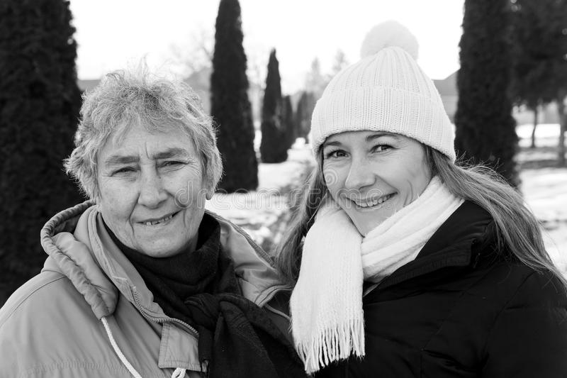 Smiling elderly woman and young caregiver. Photo of happy elderly women and young caregiver royalty free stock image