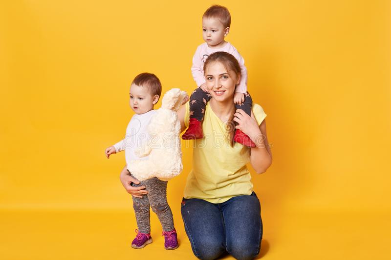 Photo of happy family. Mom with her twins girls posing in studio, mum holds one kid on shoulders, dressed casual clothes, being stock photography