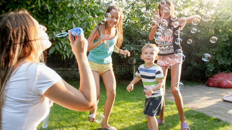 Photo of happy family playing with soap bubbles at house backyard garden. Family playing and having fun outdoors at. Image of happy family playing with soap stock images