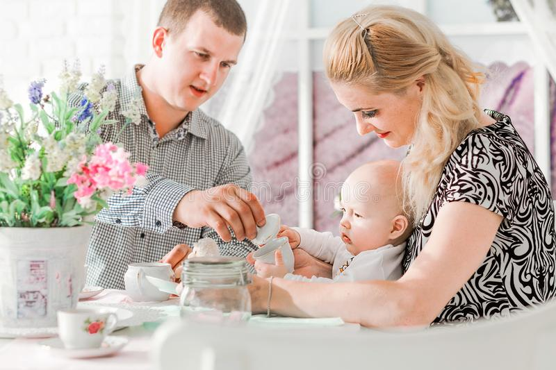 Happy family sitting with their little son at the table. Photo of happy family sitting with their little son at the table royalty free stock photos