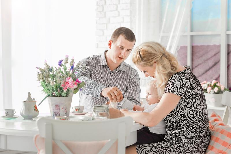 Happy family sitting with their little son at the table. Photo of happy family sitting with their little son at the table royalty free stock images