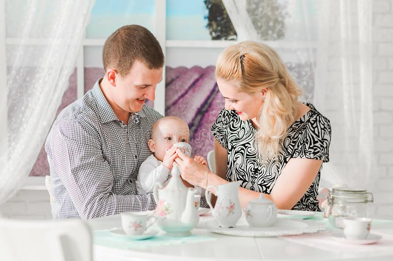 Happy family sitting with their little son at the table. Photo of happy family sitting with their little son at the table stock photo