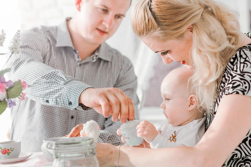 Happy family sitting with their little son at the table. Photo of happy family sitting with their little son at the table royalty free stock photo