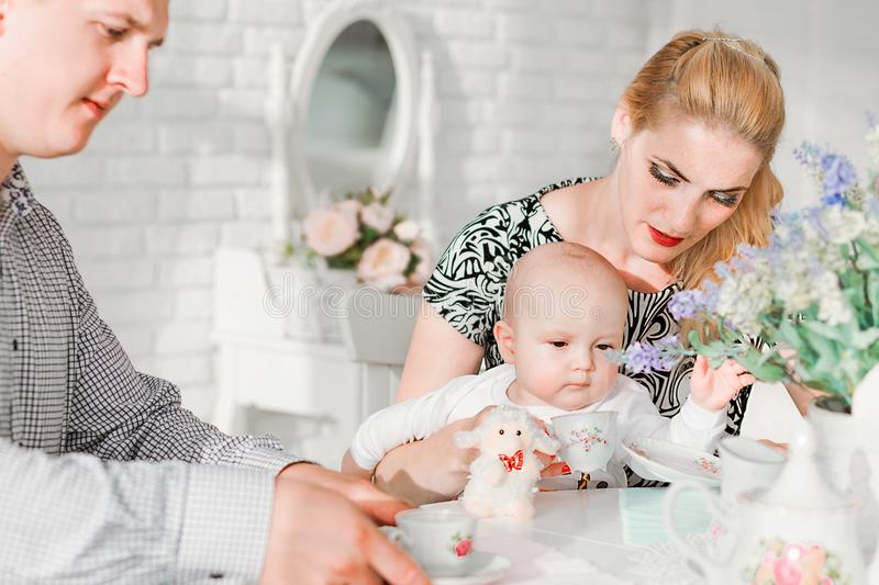 Happy family sitting with their little son at the table. Photo of happy family sitting with their little son at the table stock photos