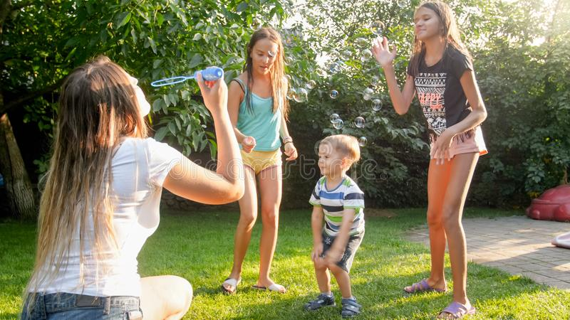 Photo of happy laughing children blowing and cathcing soap bubbles at house backyard. Family playing and having fun. Image of happy laughing children blowing and royalty free stock photography