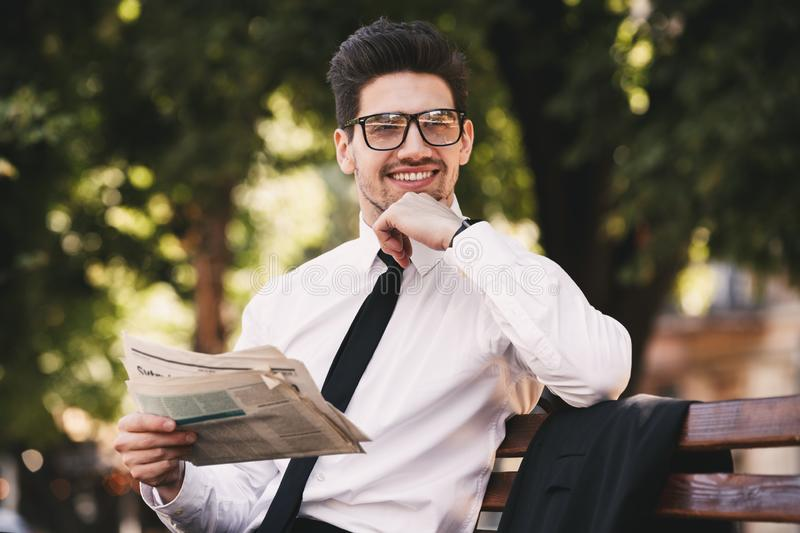 Photo of happy man in businesslike suit sitting on bench in green park, and reading newspaper during sunny day. Photo of happy man in businesslike suit sitting royalty free stock photography