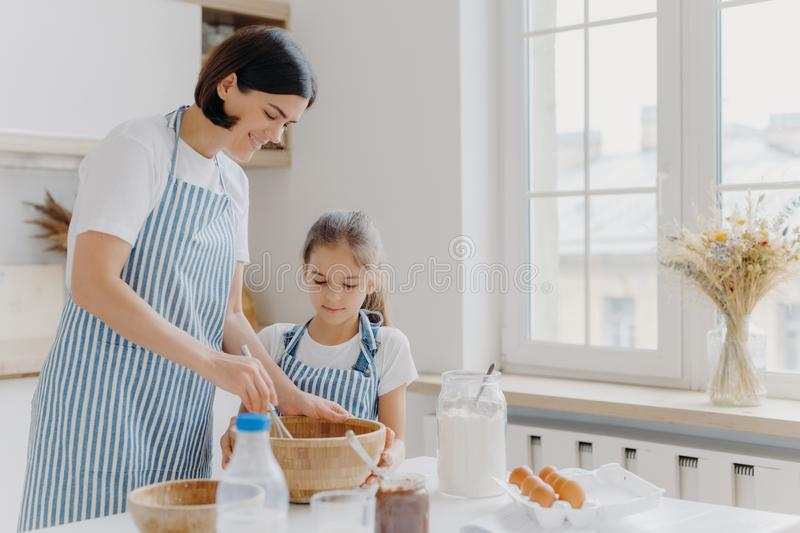 Photo of happy mum and child cook together at kitchen, wears aprons prepare something tasty, make food, whisk eggs with beater, stock photo