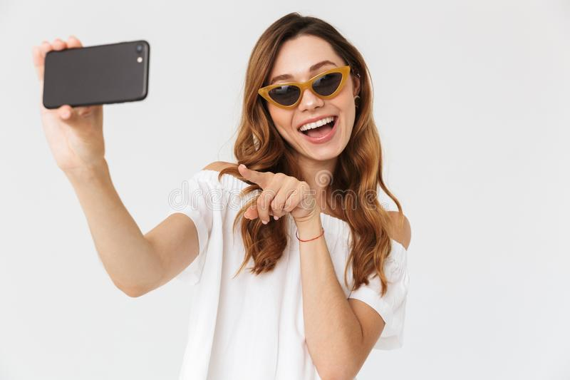 Photo of happy smiling woman 20s wearing sunglasses and jewelry royalty free stock photos