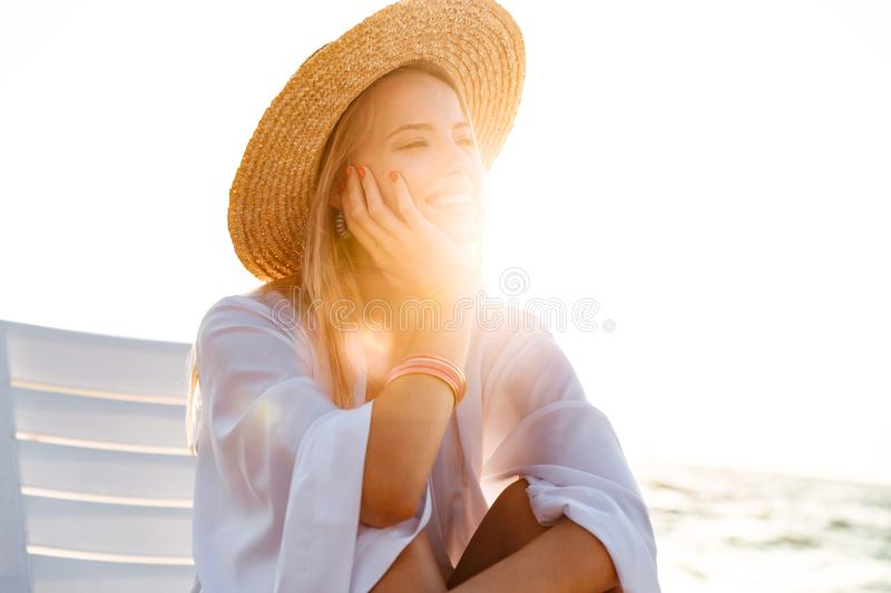 Photo of happy sunlit woman 20s in straw hat smiling, while sitting in deck chair at sea coast during summer sunrise. Photo of happy sunlit woman 20s in straw stock image