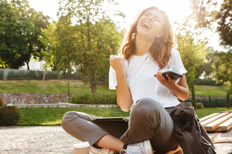 Photo of happy sunlit woman screaming and rejoicing while sitting on bench in green park on summer day, and holding smartphone stock photo