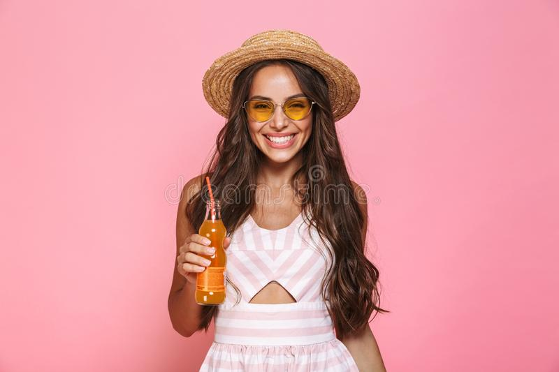 Photo of happy woman 20s wearing sunglasses and straw hat drinking juice from glass bottle, isolated over pink background royalty free stock images