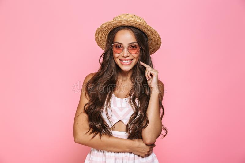 Photo of happy woman 20s wearing sunglasses and straw hat smiling at camera, isolated over pink background royalty free stock photos