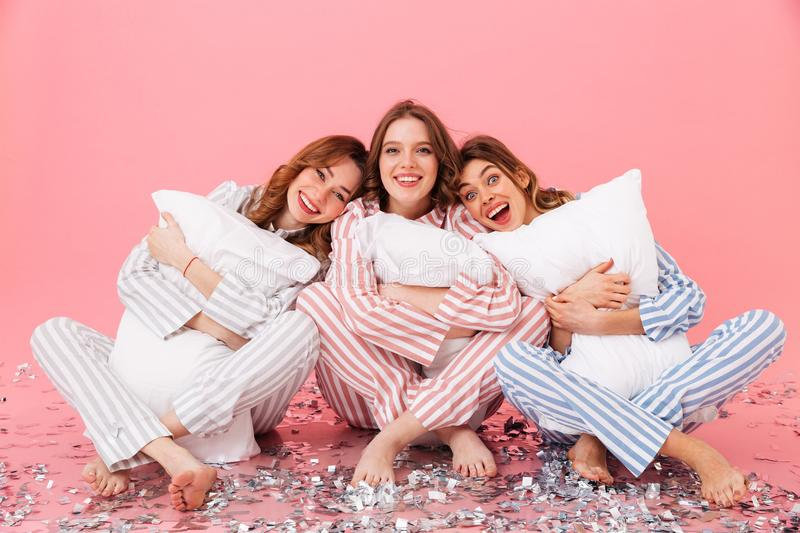 Photo of happy women 20s wearing leisure clothings sitting barefoot on floor with legs crossed and hugging pillows during girlish. Sleepover isolated over pink stock photos