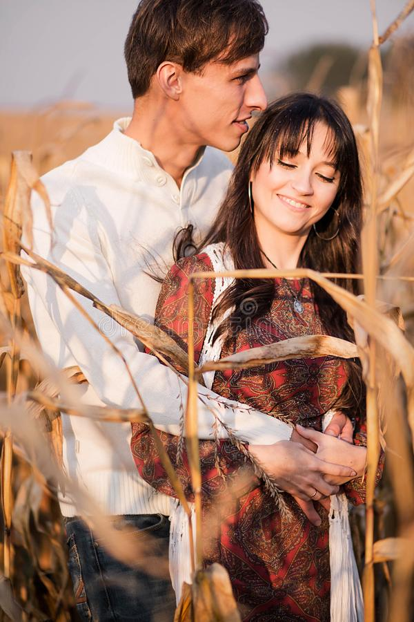 Happy young couple in autumn corn field royalty free stock photo