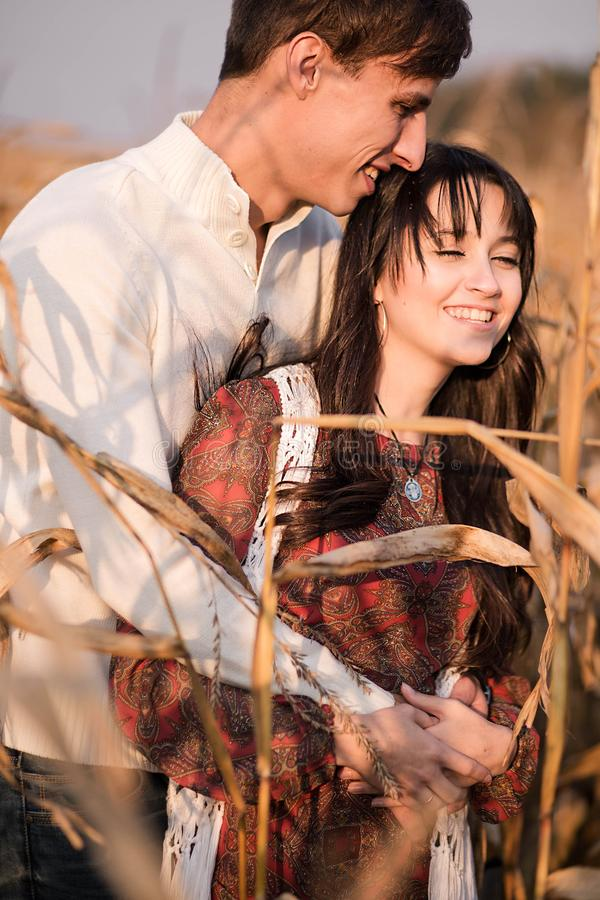Happy young couple in autumn corn field stock images