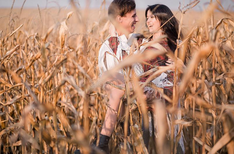 Happy young couple in autumn corn field royalty free stock image