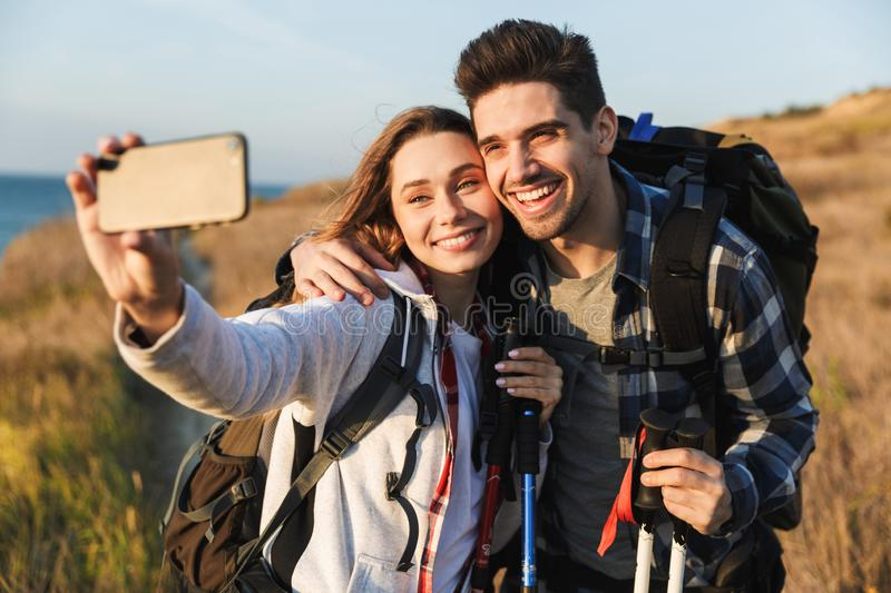 Happy young loving couple outside with backpack in free alternative vacation camping take selfie by mobile phone. Photo of happy young loving couple outside with royalty free stock images