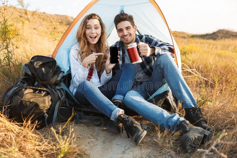 Happy young loving couple outside in free alternative vacation camping drinking hot tea. Photo of happy young loving couple outside in free alternative vacation royalty free stock photography