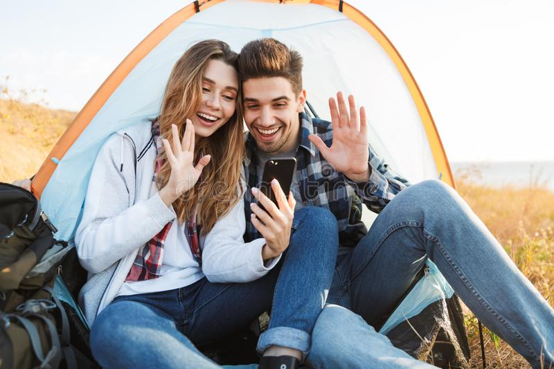 Happy young loving couple outside in free alternative vacation camping talking by mobile phone. Photo of happy young loving couple outside in free alternative stock images