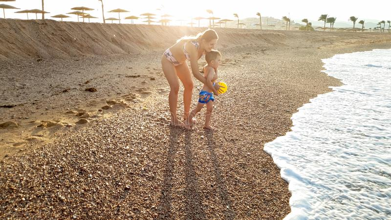 Image of happy young mother with adorable 3 years old toddler boy holding hands and walking on the sea beach against stock image
