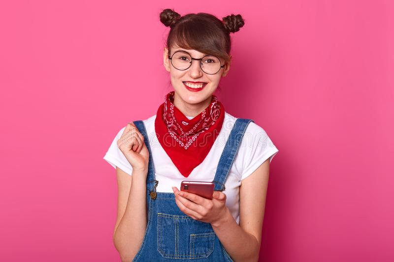 Photo of happy young teenager female with bunches, glasses, bandana on nack, dressed denim overalls and white t shirt, looks royalty free stock image
