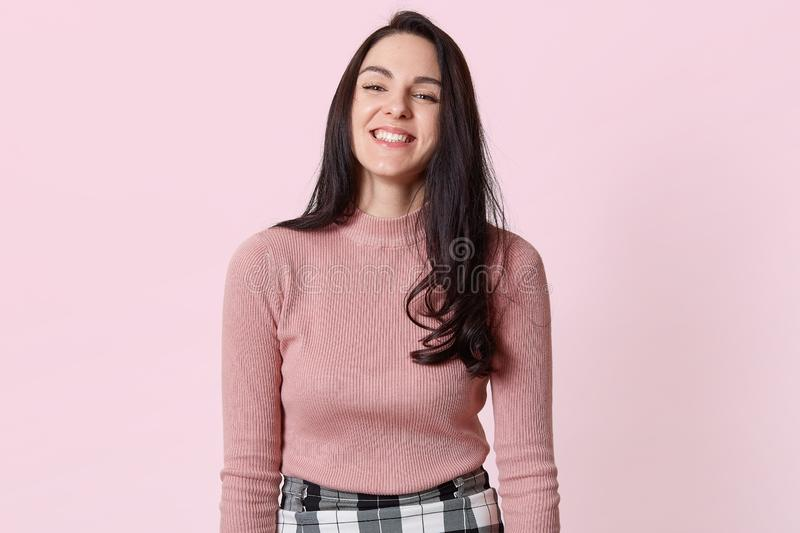 Photo of happy young woman with beautiful dark long hair laughing isolated over pink background, having fun with her friends, stock image