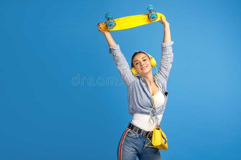 Photo of happy young woman hold yellow penny or skateboard dancing over blue background. stock photography