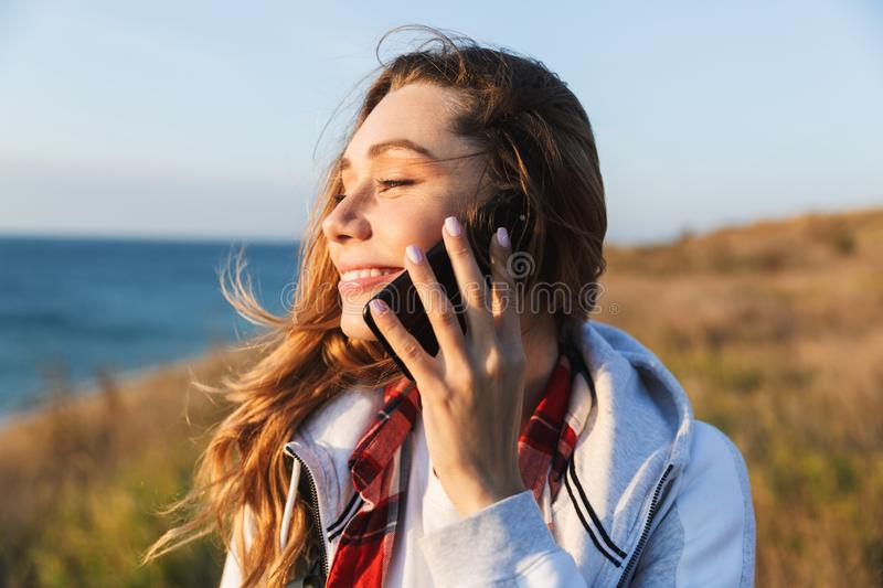 Happy young woman outside in free alternative vacation camping talking by mobile phone stock image