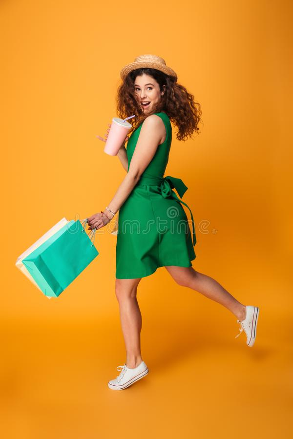 Photo of happy young woman. Standing isolated over yellow background. Looking camera drinking aerated water holding shopping bags royalty free stock photography