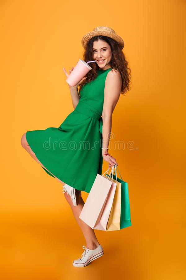 Photo of happy young woman. Standing isolated over yellow background. Looking camera drinking aerated water holding shopping bags stock image