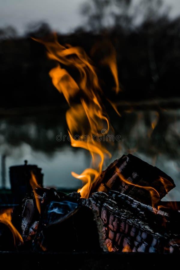 Photo haute étroite avec du feu en cheminée au lac sur le coucher du soleil photo stock