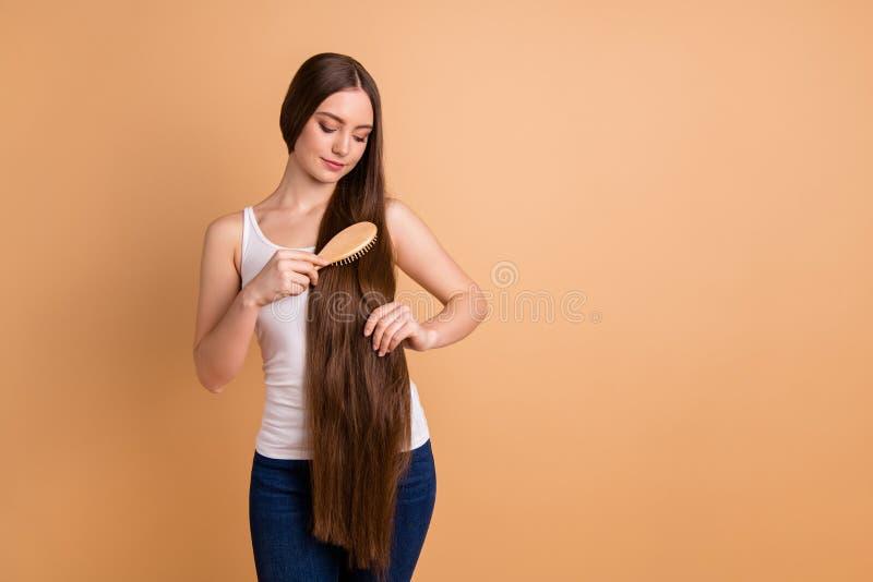 Photo haute étroite belle la stupéfiant elle dame tiennent les cheveux bruns très longs de mains de bras que le grand état courbe photo stock