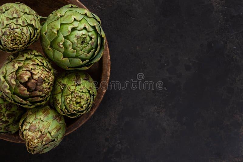 Photo haute étroite d'artichaut frais dans la vieille cuvette en bois Vue supérieure sur le fond foncé image libre de droits