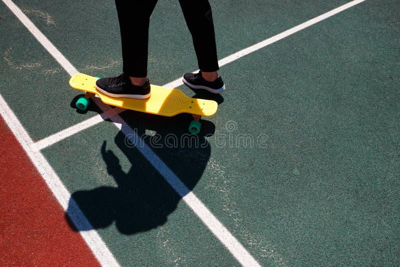 Photo haute étroite d'homme moderne dans l'usage élégant gardant des pieds sur la planche à roulettes jaune photographie stock