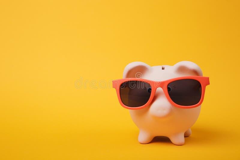Photo haute étroite de banque porcine rose d'argent avec des lunettes de soleil sur le fond jaune de mur Accumulation d'argent image stock