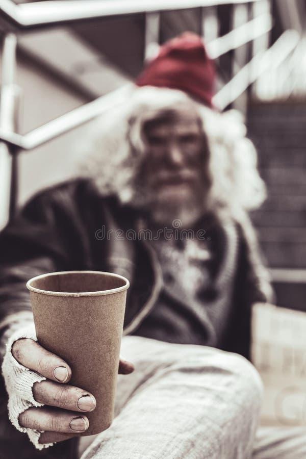 Photo haute étroite de la tasse en plastique qui se tenant par le vieil homme photographie stock
