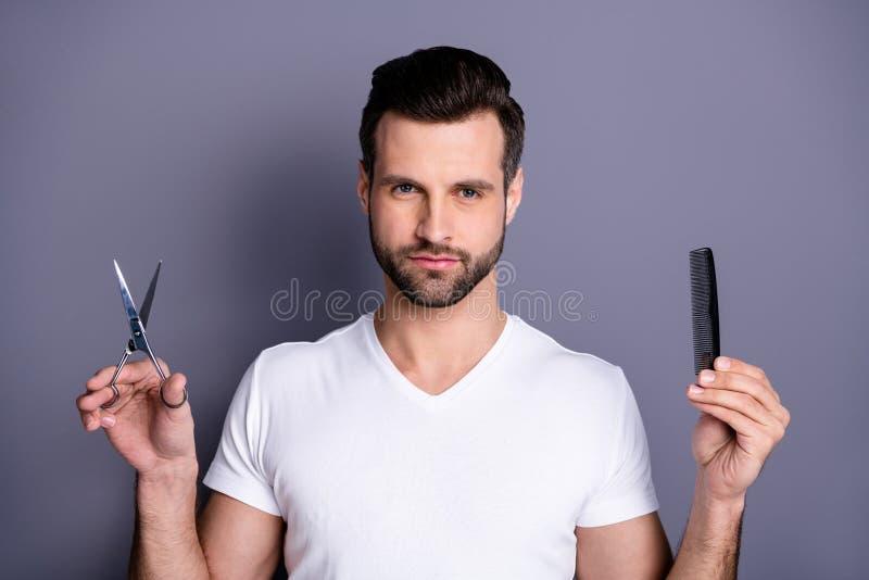 Photo haute étroite stupéfiant il il ses mains machos de ciseaux de brosse de styliste de salon de coiffure semblent le client cu photographie stock libre de droits
