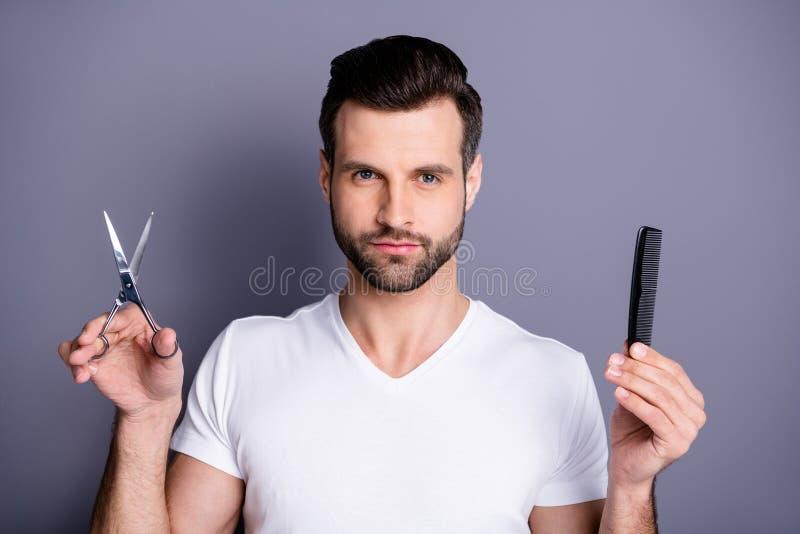 Photo haute étroite stupéfiant il il ses mains machos de ciseaux de brosse de styliste de salon de coiffure semblent le client cu images stock
