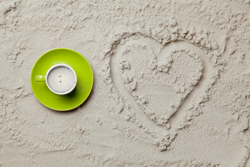 Photo of heart shaped drawing and cup of coffee on the sand. On the beach royalty free stock image