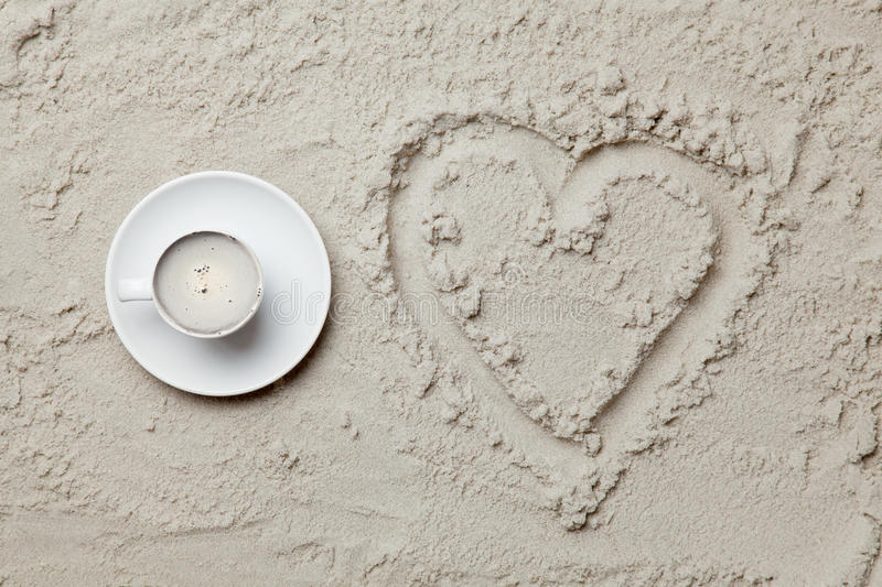 Photo of heart shaped drawing and cup of coffee on the sand. On the beach royalty free stock images
